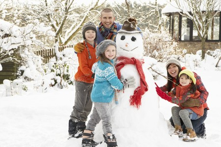 Family Building Snowman In Garden Stock Photo