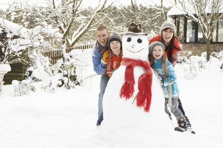 snowman: Family Building Snowman In Garden Stock Photo