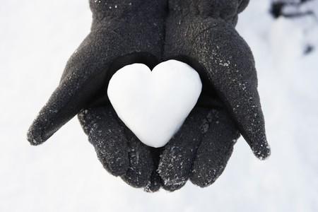 femme romantique: Fermer de mains contenant le c?ur fait de Snow  Banque d'images