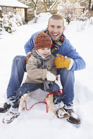 Father And Son Sitting On Sledge photo