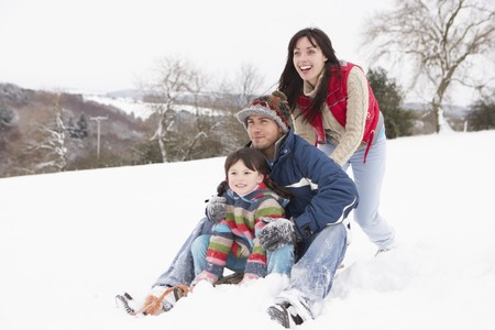 Family In Snow Riding On Sledge photo