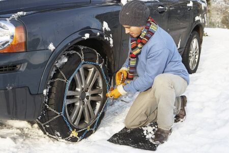 motoring: Man Putting Snow Chains Onto Tyre Of Car
