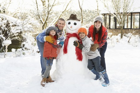 Family Building Snowman In Garden photo