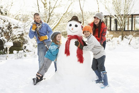Family Building Snowman In Garden Stock Photo - 7178578