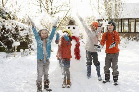 bonhomme de neige: Renforcement des enfants Bonhomme de neige dans le jardin Banque d'images
