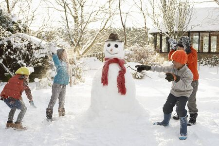 snowman: Mother And Children Building Snowman In Garden