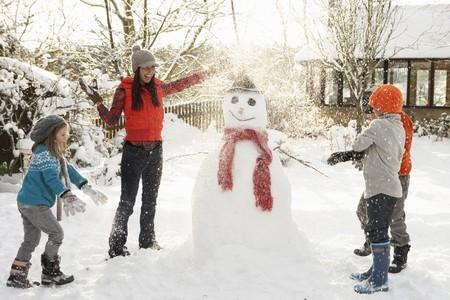 M�re et enfants Building Bonhomme de neige en jardin