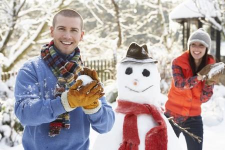 bolas de nieve: Lucha contra el joven pareja con bola de nieve en el jard�n  Foto de archivo