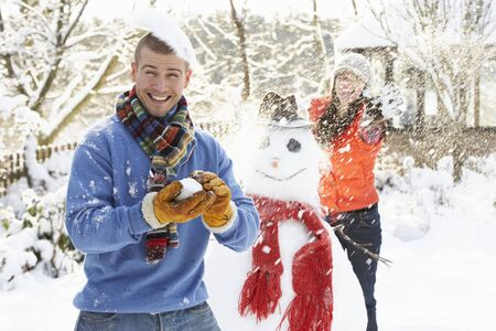 Young Couple Having Snowball Fight In Garden photo