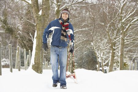 Man Pulling Sledge Through Winter Landscape photo