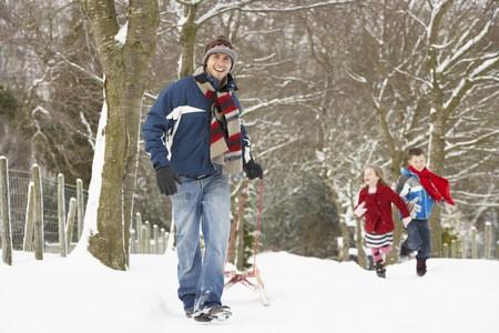 Father Pulling Children On Sledge Through Winter Landscape photo