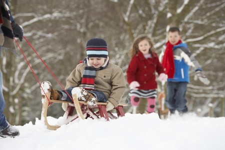 sledging people: Father Pulling Children On Sledge Through Winter Landscape Stock Photo