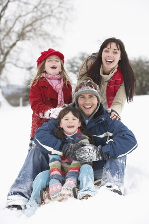 Family Having Fun In Snowy Countryside