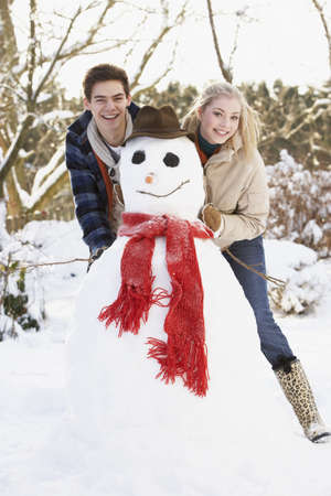 Teenage Couple Building Snowman photo