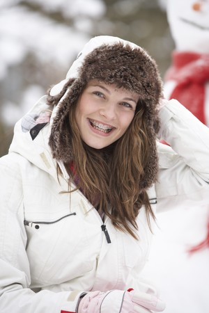 Teenage Girl Wearing Winter Clothes In Snowy Landscape photo