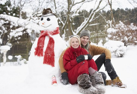 Teenage Couple In Winter Landscape Next To Snowman With Flask And Hot Drink Stock Photo - 7177668
