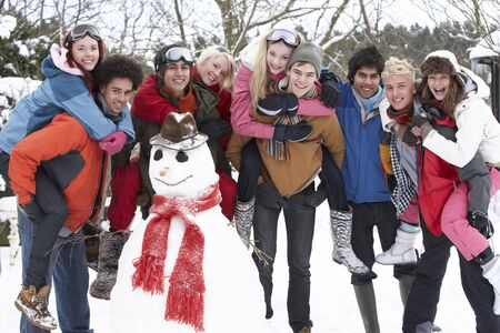 Group Of Teenage Friends Building Snowman In Garden photo
