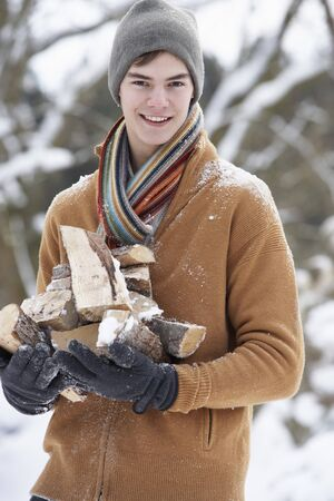 teenage boy: Teenage Boy In Snowy Landscape Carrying Logs