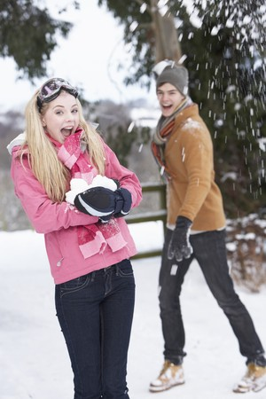 Teenage Couple Having Snowball Fight In Snowy Landscape photo