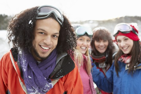 Group Of Teenage Friends Having Fun In Snowy Landscape Wearing Ski Clothing photo