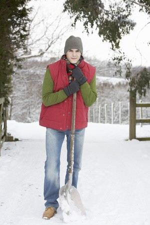 Young Man Clearing Snow From Drive photo
