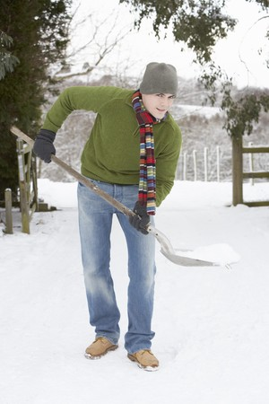 dug: Young Man Clearing Snow From Drive Stock Photo