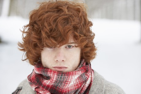 hair wrapped up: Teenage Boy Wearing Winter Clothes In Snowy Landscape