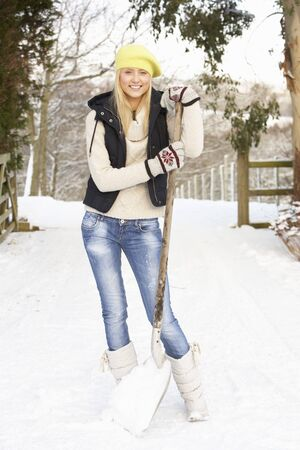 snow clearing: Teenage Girl Clearing Snow From Drive