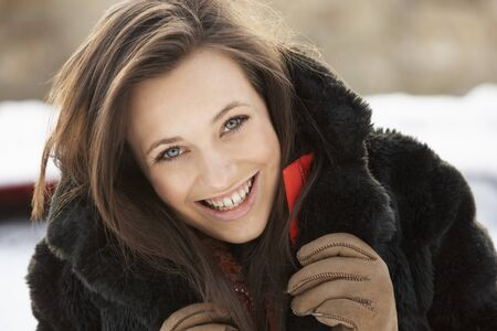 fur coat: Close Up Of Teenage Girl Wearing Fur Coat In Snowy Landscape Stock Photo