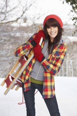 Femme contenant sledge dans le paysage Snowy  Banque d'images