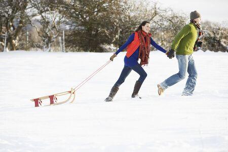 having fun in the snow: Teenage Couple Pulling Sledge Across Snowy Field