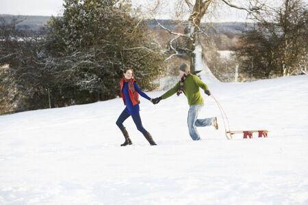 Teenage Couple Pulling Sledge Across Snowy Field photo