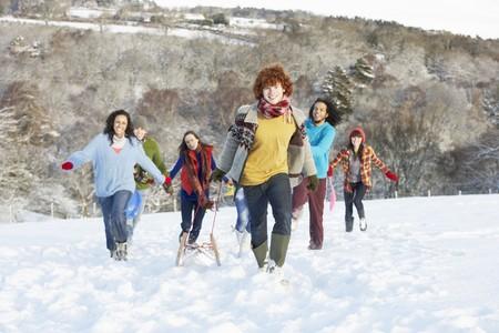 sledging: Gruppo di amici adolescente slitta nel paesaggio innevato