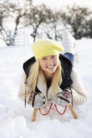 Teenage Girl Riding On Sledge In Snowy Landscape photo