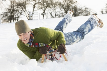 Young Man Riding On Sledge In Snowy Landscape photo