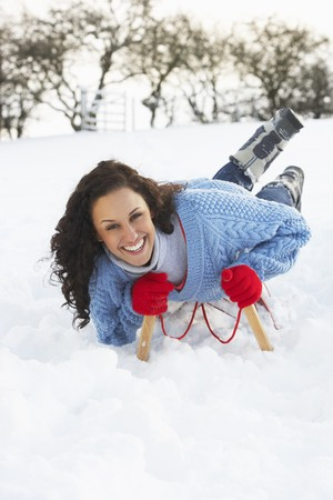 Young Woman Riding On Sledge In Snowy Landscape photo