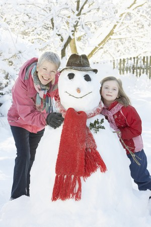 Young Girl With Grandmother Building Snowman In Garden photo