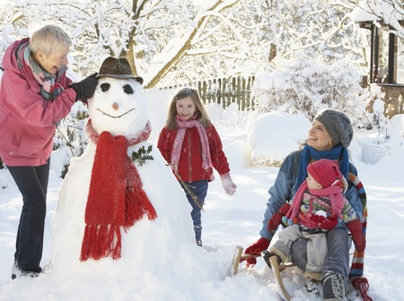 Young Girl With Grandmother And Mother Building Snowman In Garden photo
