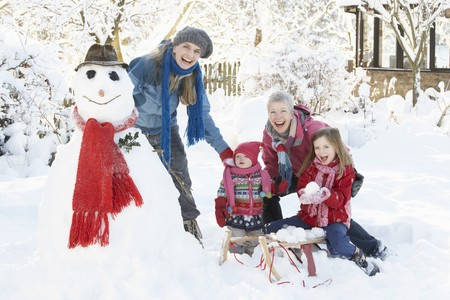 Young Girl With Grandmother And Mother Building Snowman In Garden Stock Photo - 7178373