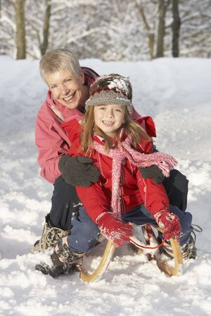 sledging people: Young Girl With Grandmother Riding On Sledge In Snowy Landscape