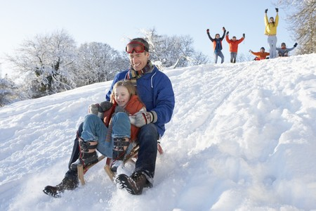 Father And Daughter Having Fun Sledging Down Hill photo