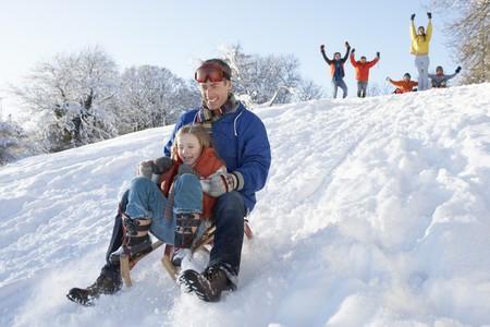 sledging: Padre e figlia divertirsi slitta Down Hill  Archivio Fotografico