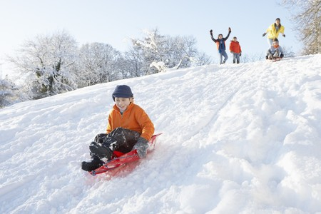 sledging people: Young Boy Sledging Down Hill With Family Watching Stock Photo