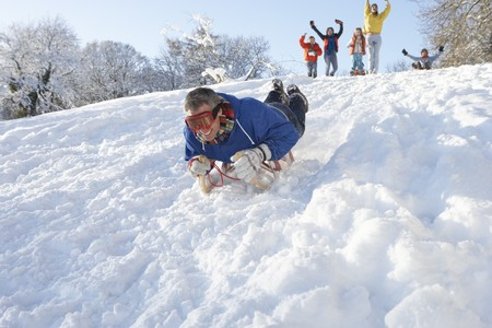 Man Sledging Down Hill With Family Watching photo