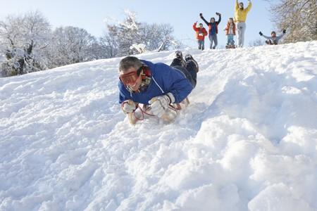 sledging: Uomo slitta Down Hill con visione dei familiari