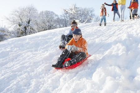 sledging: Giovane ragazzo slitta Down Hill con la visione della famiglia Archivio Fotografico