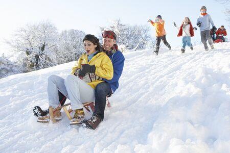 sledging: Giovani couple slittino Down Hill con visione dei familiari  Archivio Fotografico