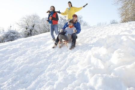Family Having Fun Sledging Down Snowy Hill Stock Photo - 7178623