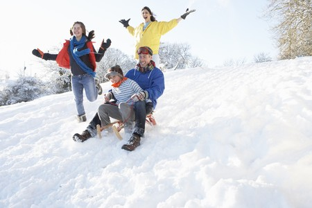 sledging people: Family Having Fun Sledging Down Snowy Hill