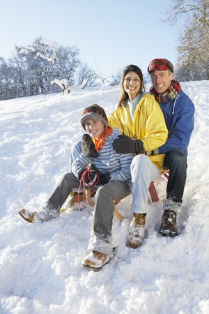Family Enjoying Sledging Down Snowy Hill photo